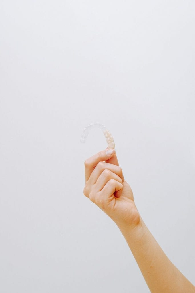 person holding up Invisalign